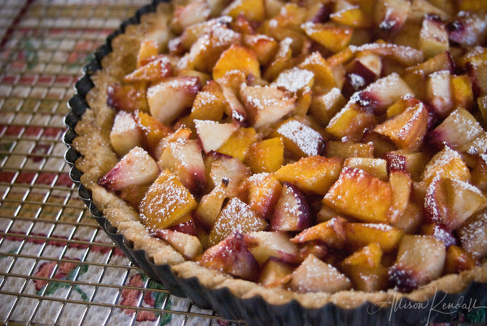 Plums, peaches and nectarines fill an almond meal tart crust, dusted with sugar and ready for baking