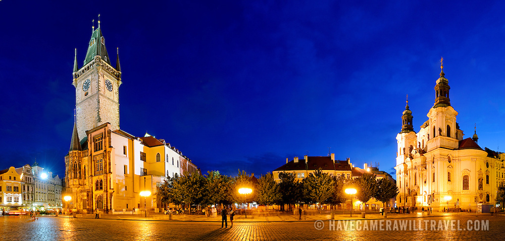 Panorama of Prague's Old Town Square at night, with St Nicholas Cathedral at right and the Old Town Hall at left