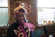 Athens resident, Dela Mensah, shows off her newly created hat at Honey for the Heart on Wednesday, October 23, 2013.