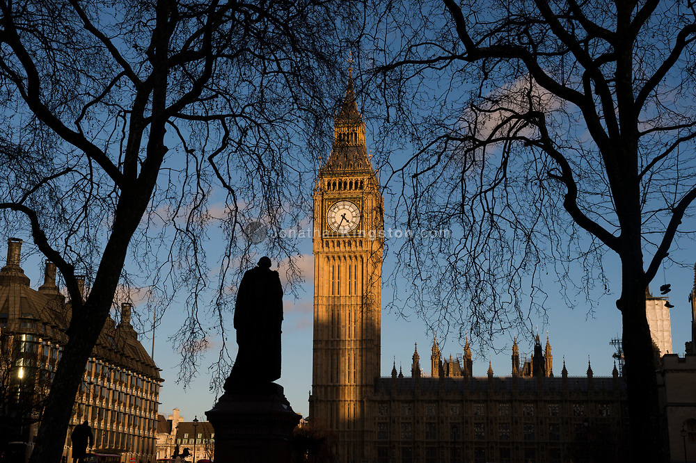 Silhouette of the statue of Benjamin Disraeli, 1st Earl of Beaconsfield, in Parliament Square with Big Ben, officially known as the Elizabeth Tower in the background.