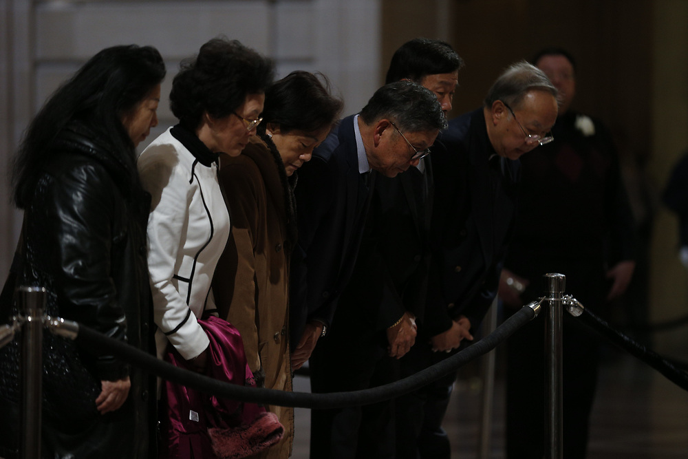 A group of people bow three times as San Francisco Mayor Ed Lee lies in state at City Hall on Friday, Dec. 15, 2017, in San Francisco, Calif. Lee died on Tuesday from a heart attack. He was 65 years old.