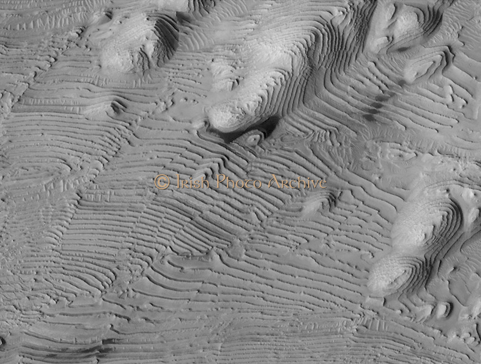 Rhythmic patterns of sedimentary layering in Danielson Crater on Mars result from periodic changes in climate related to changes in tilt of the planet. MRO.