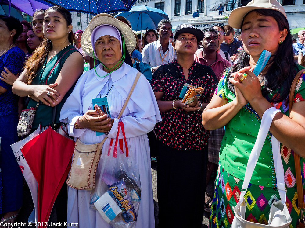 30 NOVEMBER 2017 - YANGON, MYANMAR: A nun who was not able to get into the cathedral prays with lay people during the Papal Mass at St. Mary's Cathedral in Yangon. Thursday's mass was his last public appearance in Myanmar. From Myanmar the Pope went on to neighboring Bangladesh.    PHOTO BY JACK KURTZ