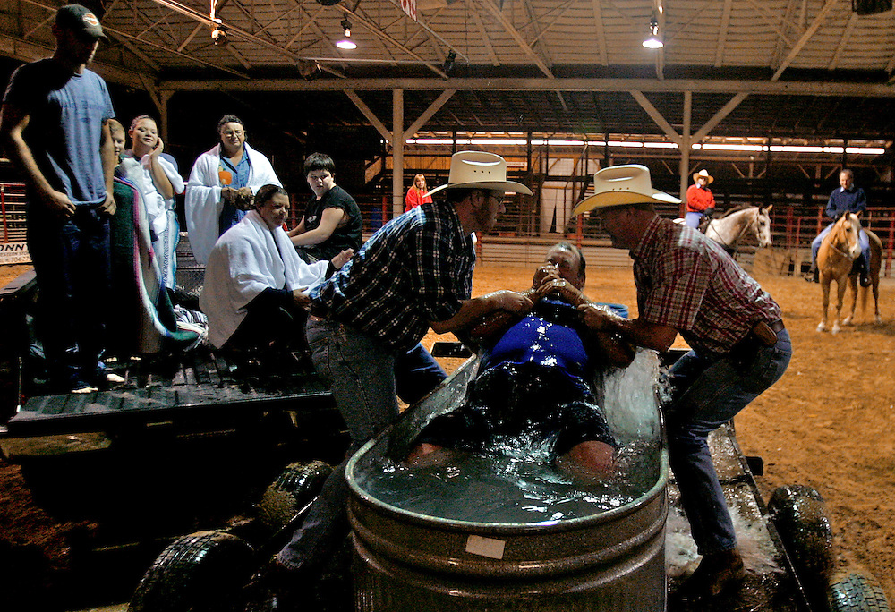 """Mike Burkett is pulled from the water in an 8-foot horse trough by pastor Jeremy Hill, left, and Jeff Smith, right, after being baptized as others, saved moments before, watch from a flatbed of a truck inside the Circle K Arena in Mount Pleasant, N.C. The Cowboy Church baptisms have become a staple of the church and a source of criticism from conventional Baptist churches. """"Some people may feel like you can't baptize in a horse trough, but it's not where, it's what the baptism means,"""" Smith says."""