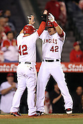 ANAHEIM, CA - APRIL 15:  Mike Trout #27 of the Los Angeles Angels of Anaheim gets a high five from Kole Calhoun #56 of the Los Angeles Angels of Anaheim after hitting a two run homer that ties the game in the bottom of the 9th inning during the game against the Oakland Athletics at Angel Stadium on Tuesday, April 15, 2014 in Anaheim, California. The Athletics won the game 10-9 in eleven innings. (Photo by Paul Spinelli/MLB Photos via Getty Images) *** Local Caption *** Mike Trout;Kole Calhoun