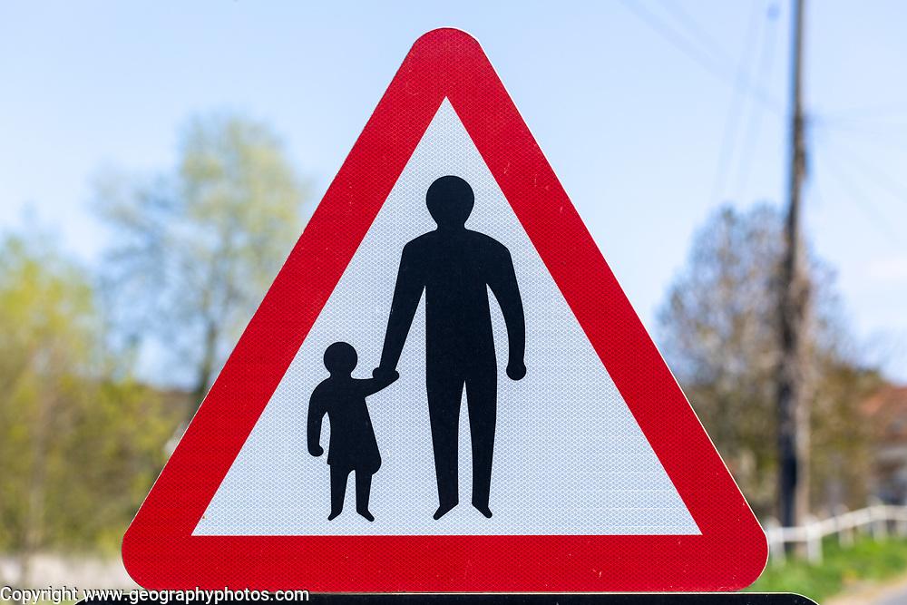 Macro close up Highway Code red triangle road sign warning of pedestrians walking, UK