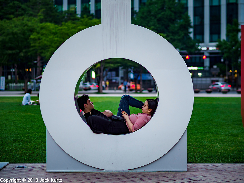 "13 JUNE 2018 - SEOUL, SOUTH KOREA: A couple relaxes in the ""O"" in the ""Seoul"" sculpture in front of the Seoul City Hall.       PHOTO BY JACK KURTZ"