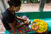 15 JUNE 2013 - YANGON, MYANMAR: A mango vendor on the Yangon Circular Train. The Yangon Circular Railway is the local commuter rail network that serves the Yangon metropolitan area. Operated by Myanmar Railways, the 45.9-kilometre (28.5mi) 39-station loop system connects satellite towns and suburban areas to the city. The railway has about 200 coaches, runs 20 times and sells 100,000 to 150,000 tickets daily. The loop, which takes about three hours to complete, is a popular for tourists to see a cross section of life in Yangon. The trains from 3:45 am to 10:15 pm daily. The cost of a ticket for a distance of 15 miles is ten kyats (~nine US cents), and that for over 15 miles is twenty kyats (~18 US cents). Foreigners pay 1 USD (Kyat not accepted), regardless of the length of the journey.     PHOTO BY JACK KURTZ