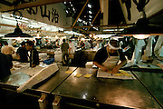 A trader works at his counter in  Tsukiji Wholesale fish market n Tokyo, Japan. May 11th 2006