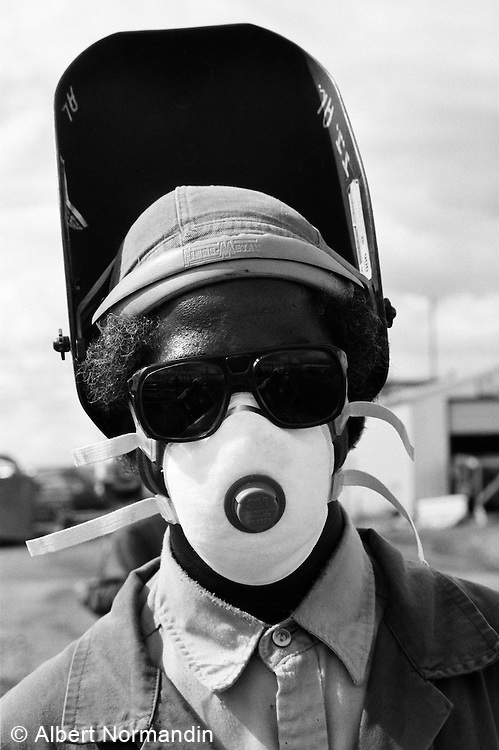 Welder on refinery plant site with goggles and mask on
