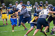 Head coach Joseph Gillespie hands the ball off during practice at Stephenville High School in Stephenville, Texas on November 5, 2013. (Cooper Neill / for The New York Times)