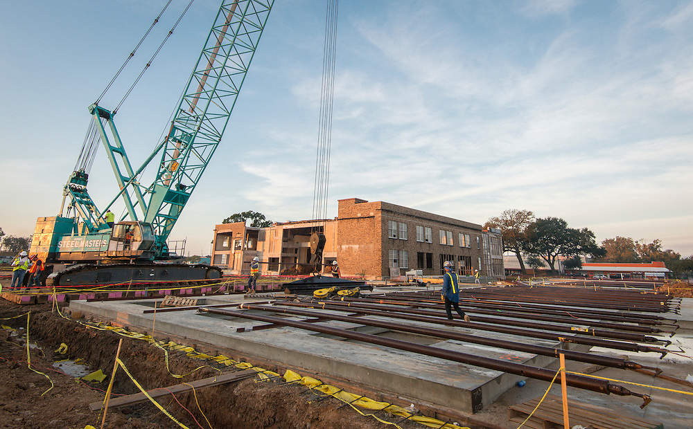 Construction crews lift the first wall of the new building at Milby High School, December 10, 2015.