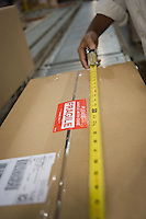 Man measuring cardboard box close-up