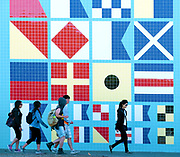 People walk in front of a tiled wall with maritime flag design Los Angeles CA