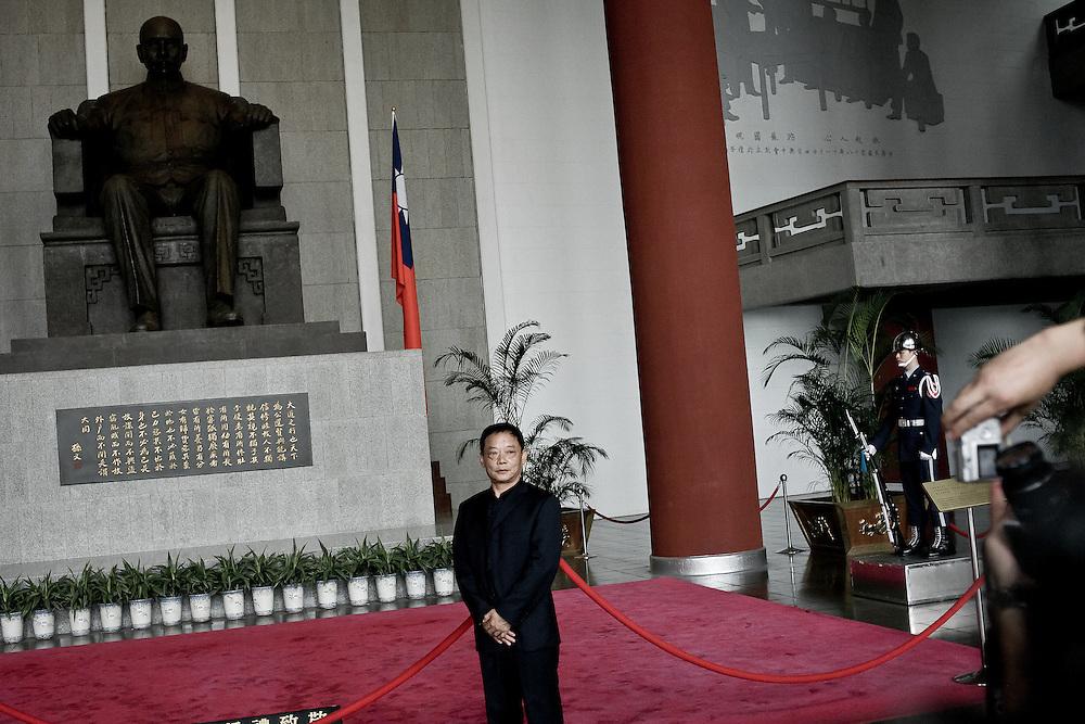 Un homme pose devant la statue du Dr Sun Yat-Sen, fondateur du Gumingdang et considéré à Taiwan (comme en Chine populaire ...) comme le père de la nation.