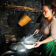 A cook preparing a bowl of pho (noodle soup) in her kitchen. The bamboo walls in the background are stained black from the smoke from the stove.