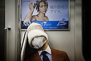 TOKYO, JAPAN, 30 MAY - A salary man sleep in the train with a mask on his face and a wooly hat on his head that could not permit us to know is identity. Just behind, a commercial for a shampoo. May 2012 [FR] Un homme en costume est endormi dans le train. Il porte un masque et un bonnet et laine. Juste derrière lui, une affiche pour un shampoing