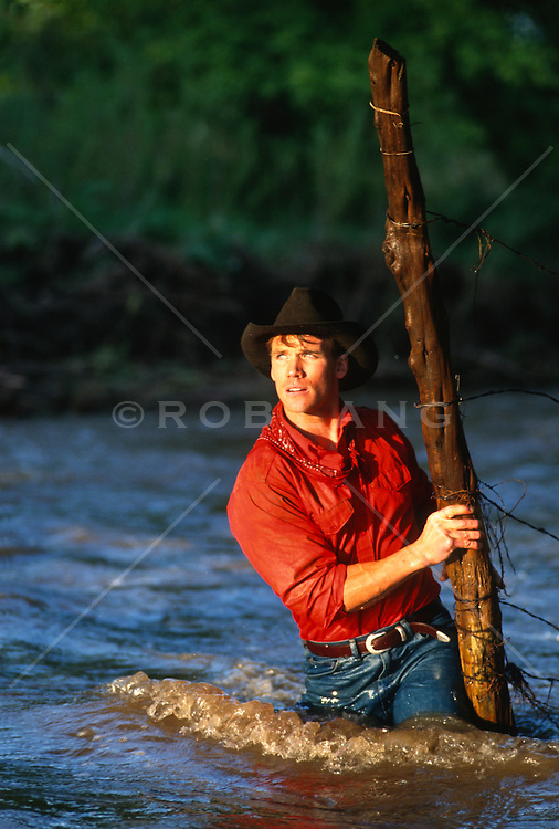 Rancher crossing a river to repair a barbed wired fence