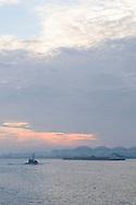 Nederland, Amsterdam, 20151028<br /> Zicht op het Noordzeekanaal bij Hembrug. De ochtend kondigt zich aan met oranje en gele kleuren door een gesloten wolkendek. Een klein schip vaart voor een binnenvaartschip. <br /> Op de achtergrond opslagtanks langs de waterkant.<br /> Chemtura een fabriek aan de Ankerweg in Amsterdam, waar onder andere gewasbeschermingsmiddelen geproduceerd worden<br /> <br /> Netherlands, Amsterdam, 20151028<br /> View of the North Sea at Hembrug. The morning announces itself with orange and yellow colors with a closed cloud cover. A small ship sails for a barge.<br /> In the background storage tanks along the waterfront.<br /> Chemtura a factory on the Ankerweg in Amsterdam, where among other plant protection products are produced