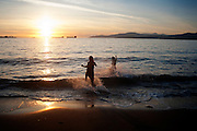 Summer 2012:<br /> <br /> Friends Tanny Lopez and Linsey McTaggart charge into the ocean at sunset on Third Beach in Vancouver's Stanley Park. <br /> <br /> (Kathleen Hinkel/photographer)