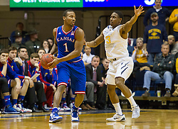 Kansas Jayhawks guard Wayne Selden Jr. (1) looks to pass while guarded by West Virginia Mountaineers guard Juwan Staten (3) during the second half at the WVU Coliseum.