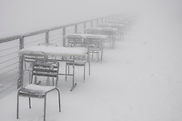 Mt. Rigi, Central Switzerland. Terrace of mountain restaurant showing the forlorn patio furniture in the mist, covered in snow.