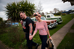 © London News Pictures. 11/05/2013. Hemsby, UK. A couple walk hand in hand dresses in 1950's outfits past classic American cars as  Rock and Roll enthusiasts gather at the Hemsby Rock 'n' Roll Weekender  in Hemsby, Norfolk. Twice a year rock and roll enthusiasts gather in the grounds of the Authentic 1950s Seacroft Holiday Site to re-live the 50's by dressing in keeping with the period and listening to live bands playing jive, hop, bop and Rock 'n' Roll. Photo credit: Ben Cawthra/LNP