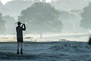 UNITED KINGDOM, London: 12 May 2020 <br /> A jogger stops to take a pictures of a frosty Richmond Park early this morning. The weather in the capital, although starting sunny and cold today, is set to be cloudy for the rest of the week.
