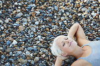 Young woman smiling lying on pebble beach elevated view