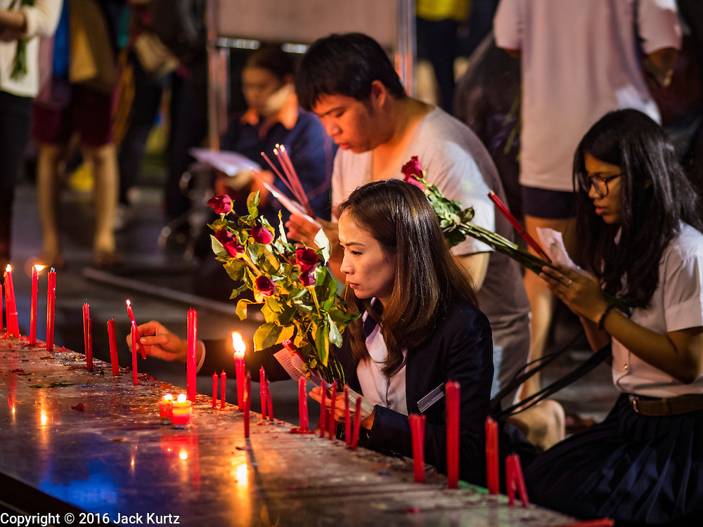 18 FEBRUARY 2016 - BANGKOK, THAILAND:  Men and women pray, holding nine red roses and sticks of incense, at the Trimurti Shrine in Bangkok. Every Thursday night, starting just after sunset and peaking at 21.30, hundreds of Bangkok single people, or couples seeking guidance and validation, come to the Trimurti Shrine at the northeast corner of Central World, a large Bangkok shopping mall, to pray to Lord Trimurti, who represents the trinity of Hindu gods - Brahma, Vishnu and Shiva. Worshippers normally bring an offering of red flowers, fruits, one red candle and nine incense sticks. It's believed that Lord Trimurti descends from the heavens at 21.30 on Thursday to listen to people's prayers. Although most Thais are Buddhists, several Hindu traditions have been incorporated into modern Thai Buddhism, including reverance for Trimurti.      PHOTO BY JACK KURTZ