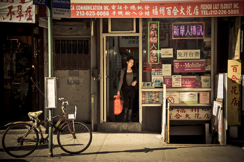 A woman gets out of a grocery store in Chinatown, Manhattan, New York, 2010.