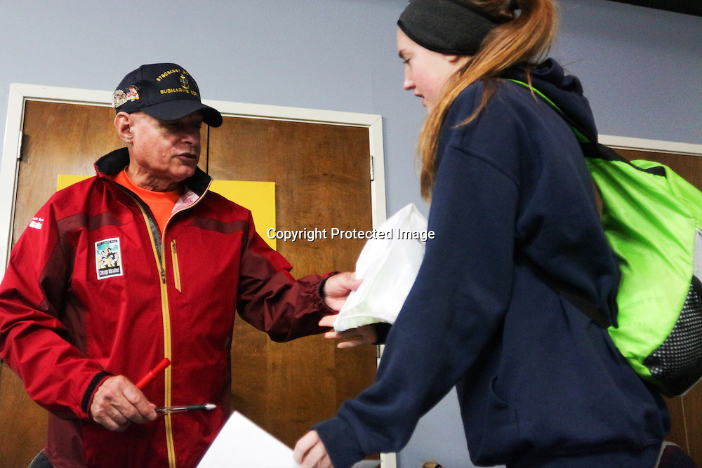Sid Busch helps Caroline Price, 16 register for the 5K race before the 16th Annual Battleship Half Marathon. (Jason A. Frizzelle)