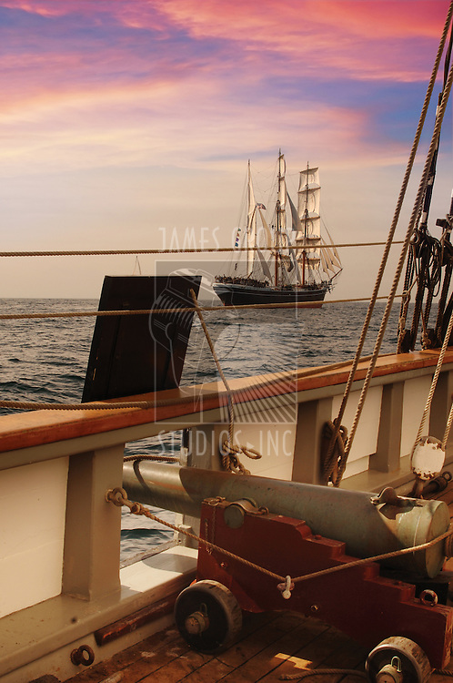 Deck of a vintage ship at dusk with a windjammer on the horizon