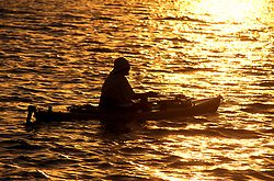 Stock photo of the silhouette of a man paddling his kayak at sunset