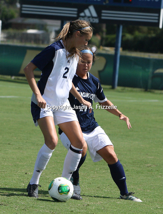 UNCW's Caroline McClain battles Longwood's Chelsea Walter for the ball.