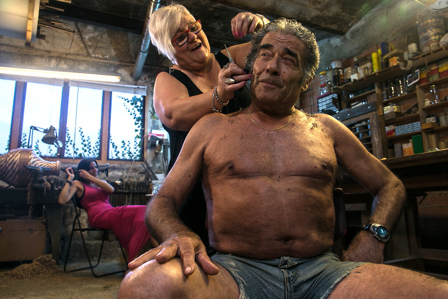 /EN/ Emilio jokes with her neighbour in the hairdressing salon that she has improvised in the middle of his workshop. <br />