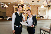 Portrait of happy waiter and waitress in restaurant
