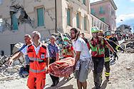 24 August 2016, Amatrice Italy - Rescuers carrying on a stretcher the lifeless body pulled from the rubble after a 6.3 earthquake hit the town of Amatrice in Lazio region killing more than 240 people. Many other towns of the italian central regions have been hit by the quake. There are still many missing people under the rubble.