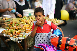 Image ©Licensed to i-Images Picture Agency. 28/07/2014. Cairo, Egypt. <br /> 61981785<br /> A young vendor sells balloons outside a mosque on the Eid al-Fitr festival in Cairo, Egypt, on July 28, 2014. Egyptian Muslims on Monday celebrate the Eid al-Fitr festival that marks the end of the fasting month of Ramadan. Picture by  imago / i-Images<br /> UK ONLY