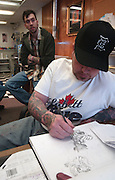 """Stay True tatoo shop owner and artist Erik Stevenson (right) works on a design for a client while his partner """"Nigel"""" talks with other customers."""