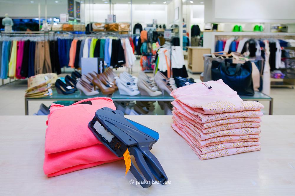Pricing, store, desk.. Price gun on folded clothes of counter in retail shop interior. Tartu, Estonia.