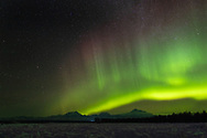 Northern Lights (Aurora Borealis) over Mount Foraker, Mount Hunter, and Denali (Mt. McKinley) in the Alaska Range in Southcentral Alaska.Winter.