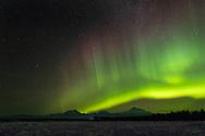 Northern Lights (Aurora Borealis) over Mount Foraker, Mount Hunter, and Denali (Mt. McKinley) in the Alaska Range in Southcentral Alaska.Winter.