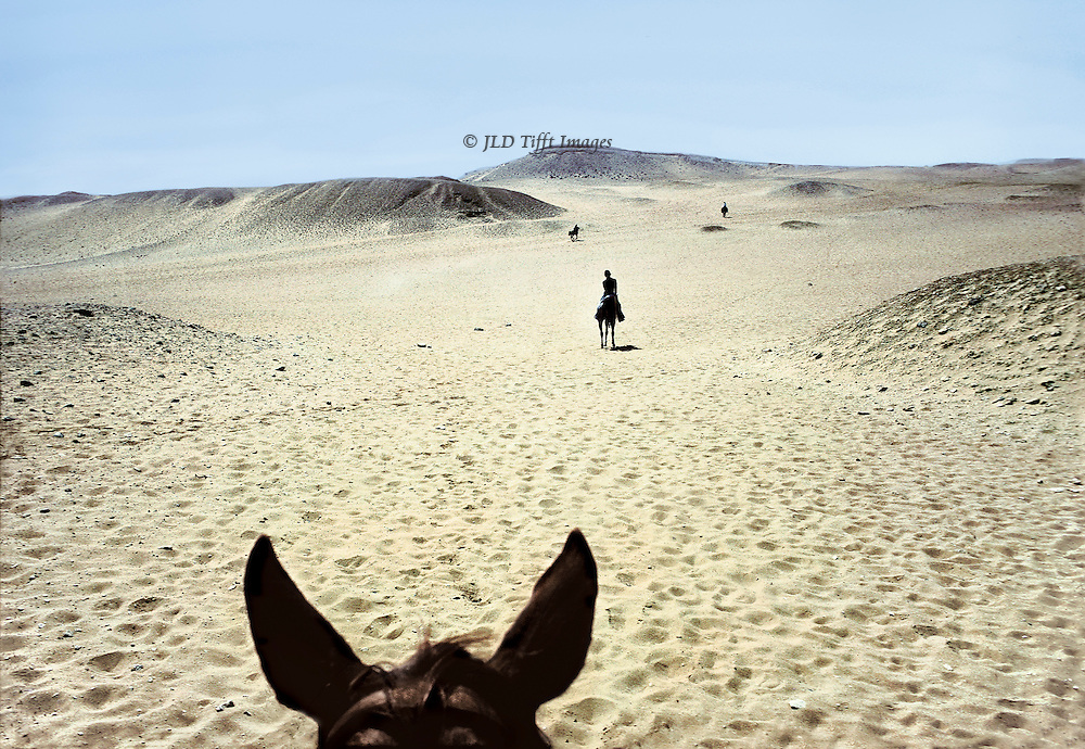 From the rider's point of view, horse's ears in the foreground, two other riders in the distance ahead.  Endless sand on all sides; slight hills on the horizon.  Short shadows; it is high noon; pale blue sky.