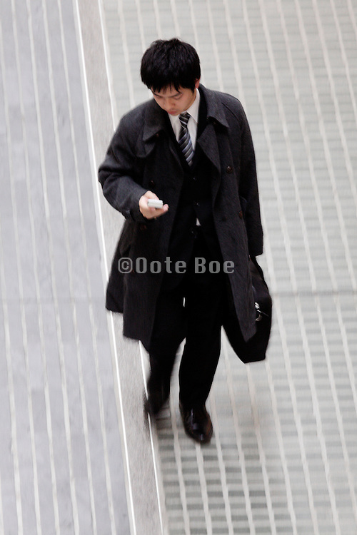 young adult businessman checking his mobile phone while walking