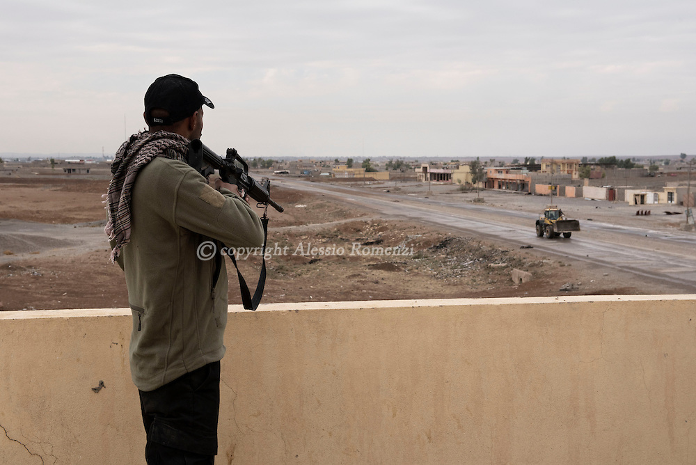 Iraq, Bazwaia: Fearing an attack by explosive vehicle, an Iraqi army fighter aims at a bulldozer as it gets closer without being recognised . Alessio Romenzi