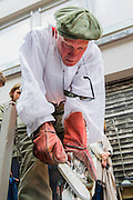 A cast of a horses head is cleaned up after it cools and is broken from its mould - Nic Fiddian-Green (pictured in white shirt - sculptor of monumental neo-classical horses heads) sets up his iron foundry in Bruton Place, Mayfair to demonstrate the ancient art of 'lost wax' casting and also hand patinating.  He also has a new solo show at Sladmore Contemporary from 10th June until 31st July 2015. The exhibition will include a recreation of the artist's hilltop surrey studio and workshop,  with new work in  progress.