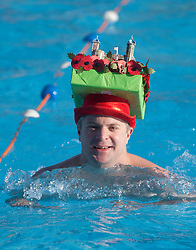 © Licensed to London News Pictures. 24/01/2015. London, UK. A contestant wears a poppy-themed hat at the 6th UK Cold Water Swimming Championships at Tooting Bec Lido, south London. Over, 650 swimmers will take the plunge to compete in a variety of chilly races.  Photo credit : Isabel Infantes / LNP