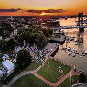 The sun sets during a concert in Prescott Park in Portsmouth, NH. The Piscataqua River and Memorial bridge are at the right.