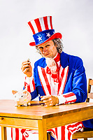 An Uncle Sam character seated at a table with a piggy bank holding up a coin in his hand in a positive way as if promoting saving and good money management.